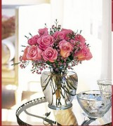 Twelve roses with waxflower in a classic glass vase.